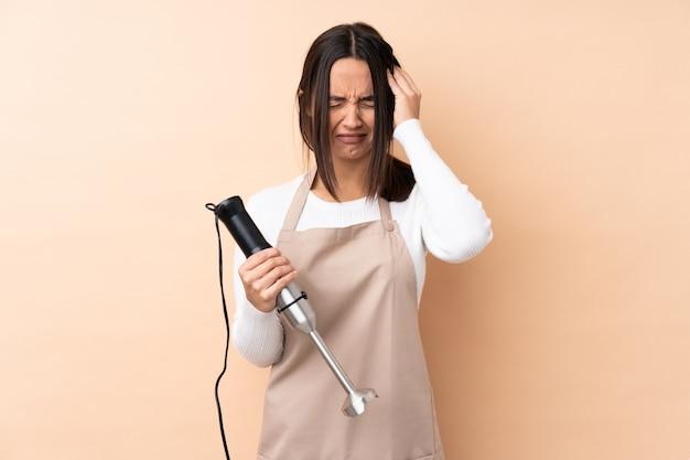 Giovane ragazza castana che usando il miscelatore della mano sopra la parete isolata con l'emicrania