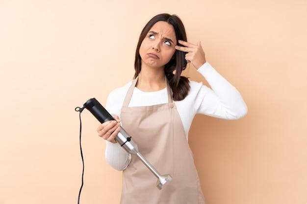 Giovane ragazza castana che usando il miscelatore della mano sopra la parete isolata con i problemi che fanno gesto di suicidio