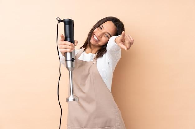 Giovane ragazza bruna che usa il frullatore a immersione isolato