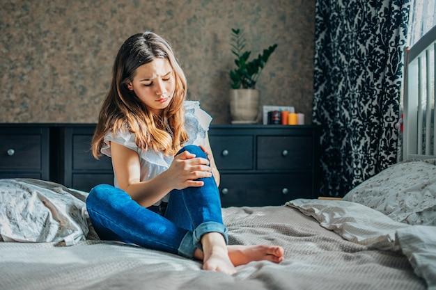Giovane ragazza bruna in una camicetta bianca e jeans blu si siede su un letto nella sua stanza, stringendo un ginocchio dolorante