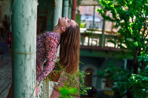 Giovane ragazza bruna con i capelli lunghi e la testa gettata all'indietro sul balcone di legno in una vecchia casa