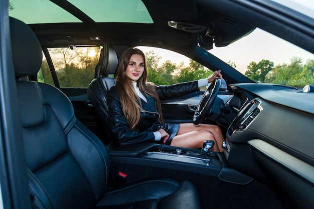 Giovane ragazza bruna con i capelli lunghi in una giacca di pelle nera e una gonna con belle gambe alla guida di un'auto costosa. giovane ragazza alla guida di un'auto