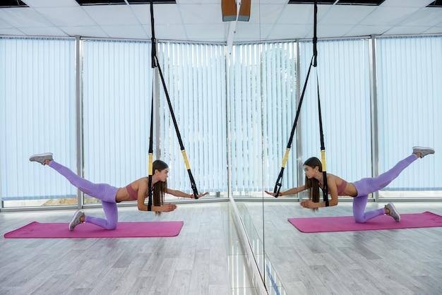 Giovane istruttore bruna che si esercita con trx in studio di aerobica. allenamento funzionale. stile di vita sportivo