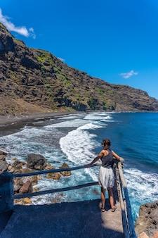Una giovane brunetta guardando dal punto di vista sulla spiaggia di nogales a est dell'isola di la plama, isole canarie. spagna