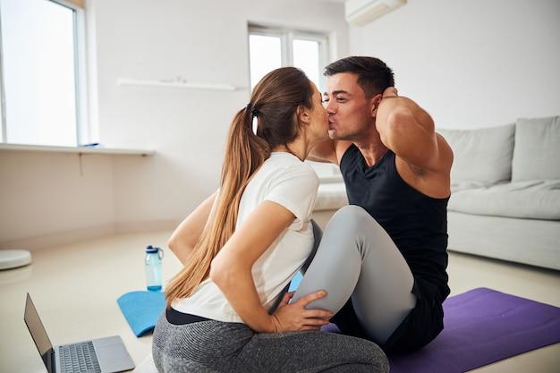 Giovane uomo bruna che riceve baci dalla fidanzata per fare addominali