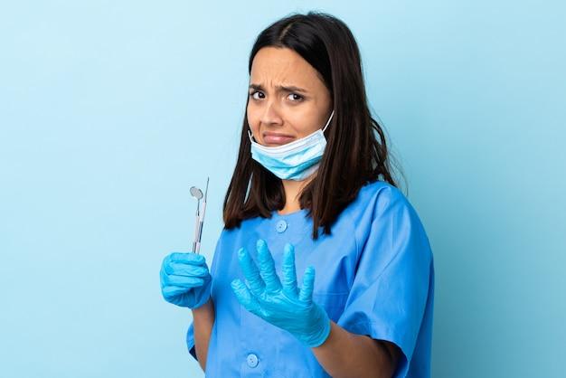 Strumenti di tenuta della giovane donna del dentista della corsa mista del brunette sopra le mani d'allungamento nervose della parete