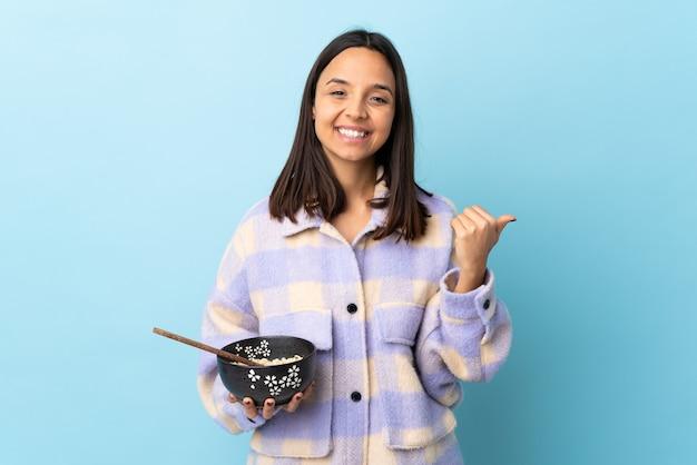 Giovane donna bruna di razza mista che tiene una ciotola piena di spaghetti isolati