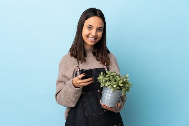 Giovane donna bruna di razza mista che tiene una pianta isolata
