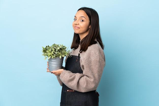 Giovane donna bruna di razza mista che tiene una pianta