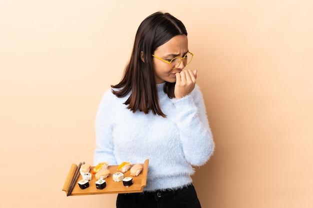 Giovane donna bruna di razza mista che tiene sushi su sfondo isolato avendo dubbi doubt