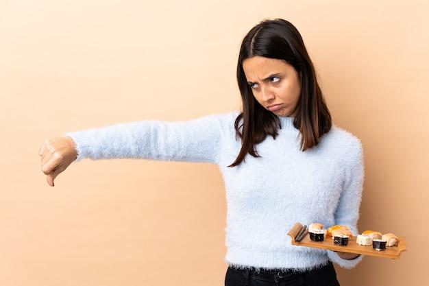 Sushi castana della tenuta della donna della giovane corsa mista sopra il pollice di mostra isolato giù con l'espressione negativa