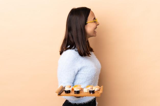 Giovane donna castana della corsa mista che tiene sushi isolato