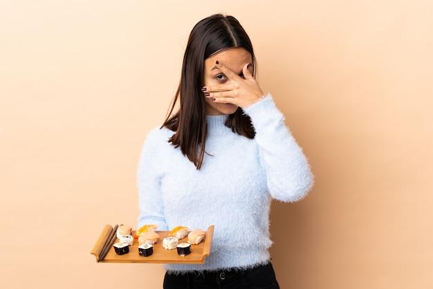 I giovani sushi della tenuta della donna della corsa mista del brunette sopra il rivestimento murale osservano a mano e sorridendo