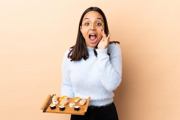 Sushi castana della tenuta della donna della giovane corsa mista sopra la parete che grida con la bocca spalancata