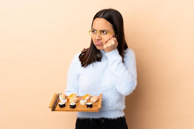 Sushi castana della tenuta della giovane donna della corsa mista sopra la parete con l'espressione stanca e annoiata