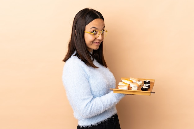 Sushi della holding della donna della corsa mista del giovane brunette