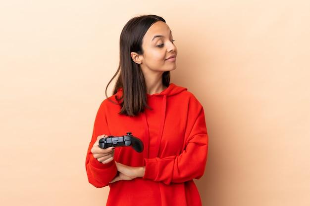 Giovane donna castana della corsa mista che gioca con un regolatore del videogioco sopra isolato pensando un'idea