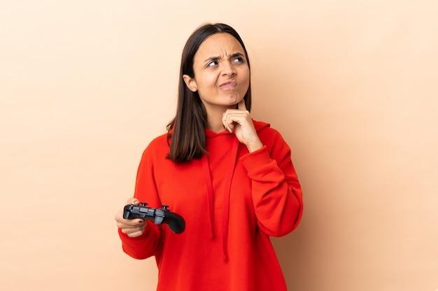 Giovane donna castana della corsa mista che gioca con un regolatore del videogioco sopra la parete isolata che pensa un'idea