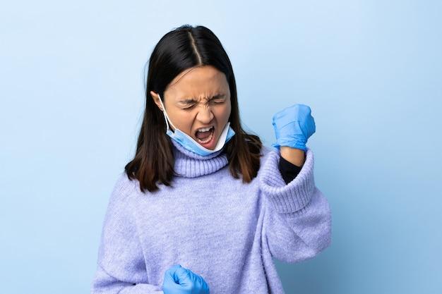 Giovane donna castana della corsa mista che protegge dal coronavirus con una maschera e guanti sopra la parete blu isolata che celebra una vittoria