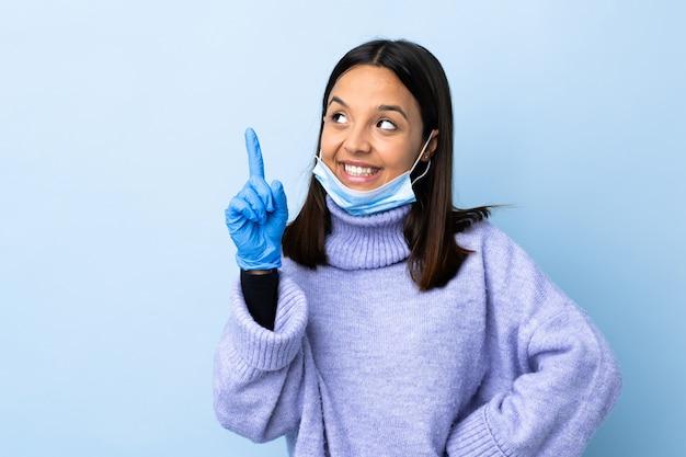Giovane donna castana della corsa mista che protegge dal coronavirus con una maschera e guanti sopra la parete blu isolata che indica su una grande idea