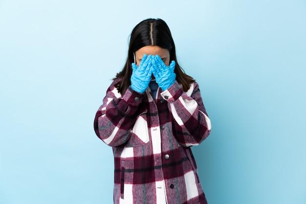 Giovane donna castana della corsa mista che protegge dal coronavirus con una maschera e guanti sopra la parete blu isolata con espressione stanca e malata
