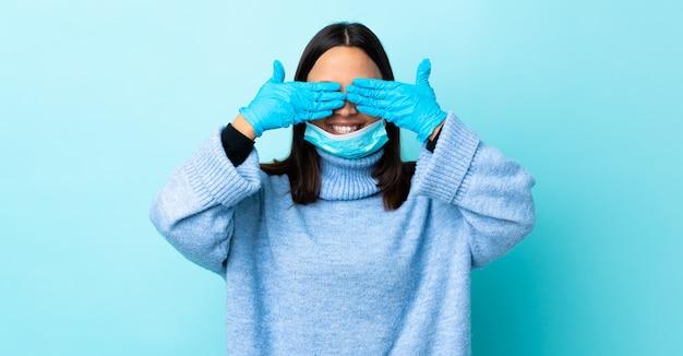 La giovane donna della corsa mista del brunette che protegge con una mascherina e guanti sopra la copertura blu della parete osserva a mano e sorridendo