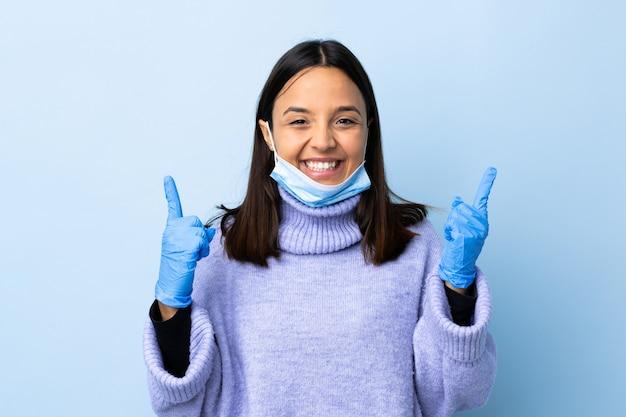 Giovane donna castana della corsa mista che protegge con una maschera e guanti sopra la parete blu che indica su una grande idea