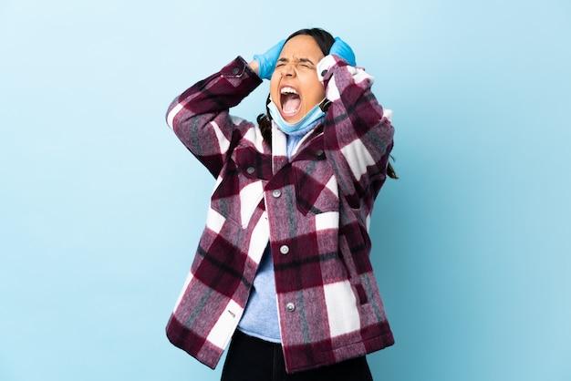 La giovane donna della corsa mista del brunette che protegge con una mascherina e guanti sopra la parete blu ha sollecitato enorme