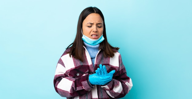 Giovane donna castana della corsa mista che protegge con una maschera e guanti sopra la parete blu che soffre dal dolore nelle mani
