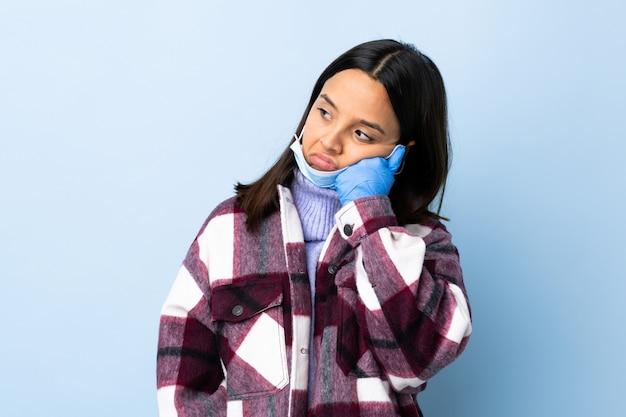 Giovane donna castana della corsa mista che protegge con una maschera e guanti sopra la parete blu con l'espressione stanca e annoiata