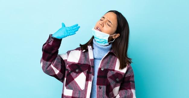 Giovane donna castana della corsa mista che protegge con una maschera e guanti sopra la parete blu con l'espressione stanca e malata