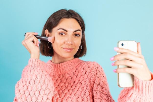 Giovane bruna in maglione rosa isolato sulla parete blu