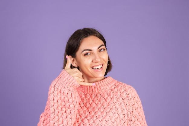 Giovane bruna in maglione rosa isolato sulla parete viola