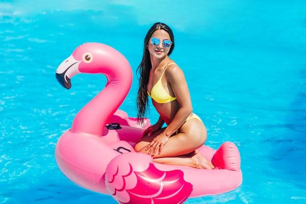 Giovane ragazza bruna e sexy divertirsi e ridere e divertirsi in piscina su un fenicottero rosa gonfiabile in costume da bagno e occhiali da sole in estate.