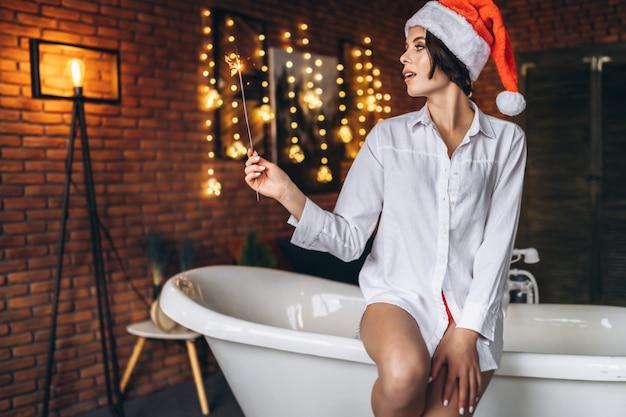 Una giovane bruna seduta sul bordo del bagno in cappello di natale che tiene la luce bengala bruciante del fuoco d'artificio sparkler nelle mani