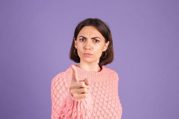 Giovane bruna in maglione isolato sulla parete viola