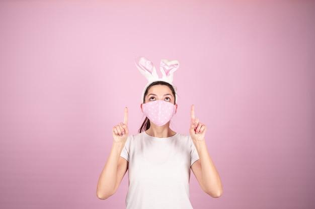 La giovane brunetta indossa orecchie da coniglio e maschera protettiva guarda in alto e punta le dita verso qualcosa. concetto di vacanze di pasqua. sfondo rosa con copia spazio. foto di alta qualità