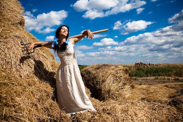 Giovane bruna in un abito bianco sta con un forcone di fieno in un campo in una limpida giornata estiva