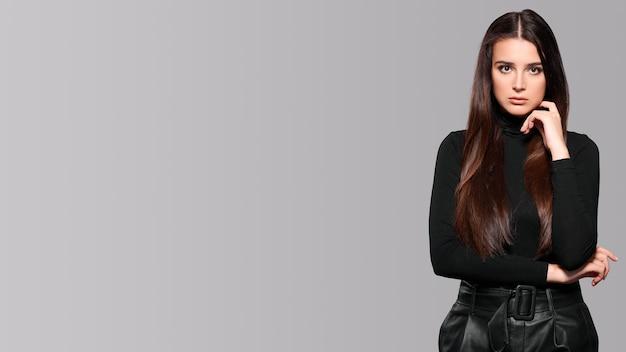 Giovane bruna con i capelli lunghi su sfondo grigio isolare. foto di alta qualità