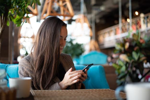 Giovane castana con lo smartphone a disposizione al ristorante con vago
