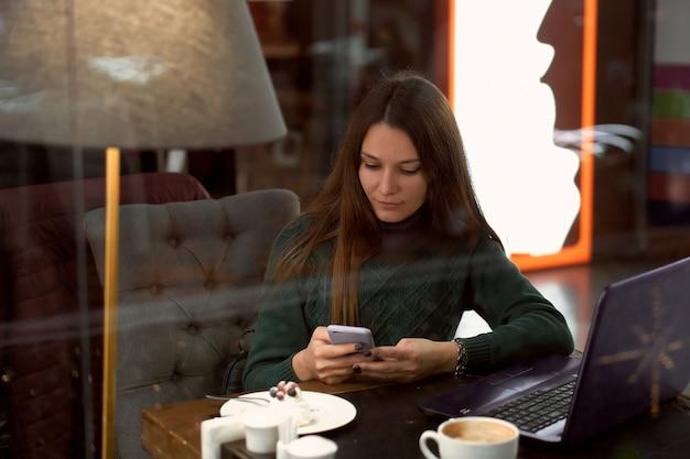 Giovane donna castana nella caffetteria con il computer portatile comunica tramite smartphone