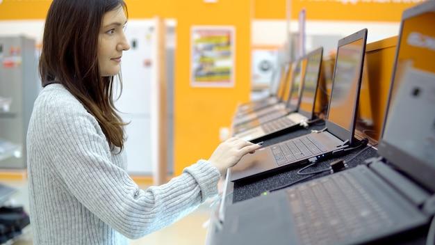 La giovane donna castana sceglie un computer portatile in un negozio di ferramenta.