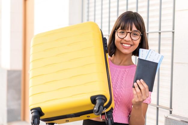 Giovane donna bruna in città in vacanza con valigia e passaporto