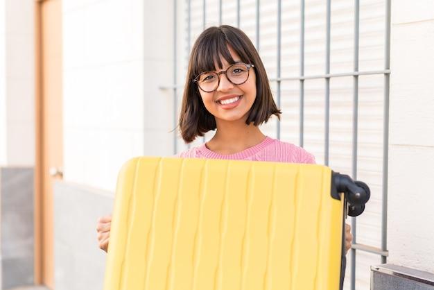 Giovane donna bruna in città in vacanza con valigia da viaggio