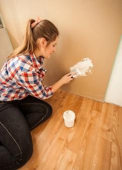 Giovane donna bruna che fa lavori di ristrutturazione della casa