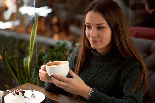 Giovane donna castana che beve caffè in un caffè e mangia il dessert