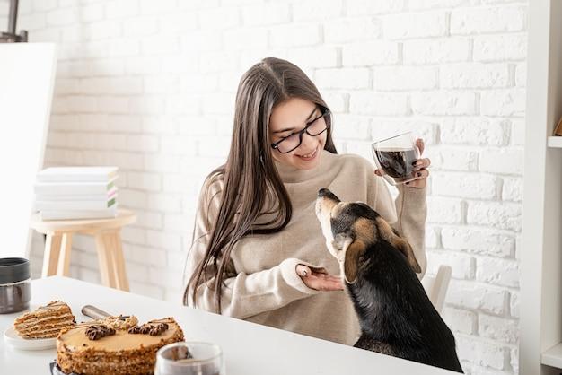 Giovane donna castana che beve caffè nero caldo che si siede al tavolo bianco