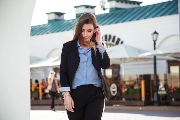 Giovane donna castana in vestito convenzionale che cammina vecchia città. ragazza indossata in camicia blu e giacca nera.