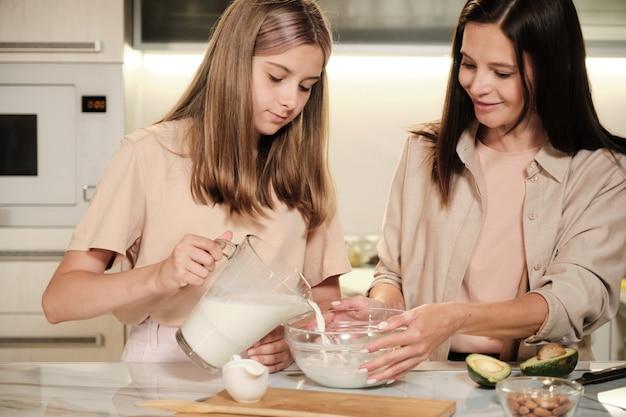 Giovane donna castana che tiene la ciotola mentre sua figlia versa il latte prima di mescolarlo con frutta fresca tagliata durante la preparazione del gelato