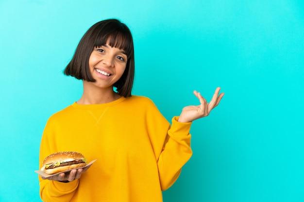 Giovane donna bruna che tiene un hamburger su sfondo isolato estendendo le mani di lato per invitare a venire